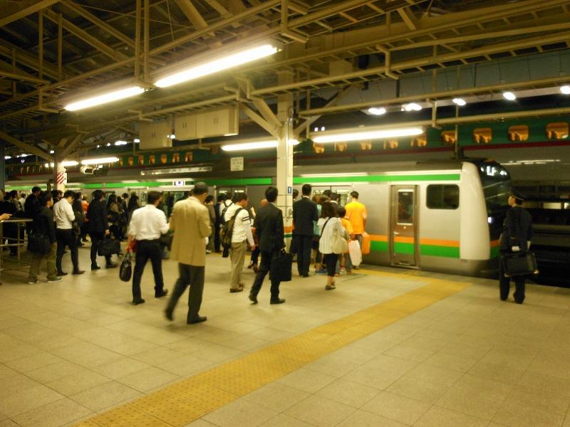 東京で始発の通勤快速を待つ人々